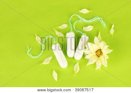 cotton tampons with yellow flower on green background close-up