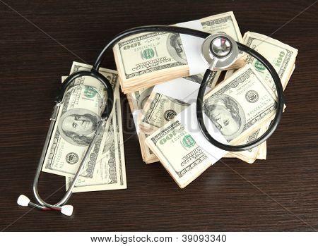 Concepto de costo de atención médica: estetoscopio y dólares sobre fondo de madera