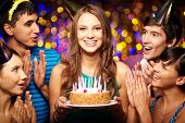 stock photo of congrats  - Portrait of joyful girl holding birthday cake surrounded by friends at party - JPG