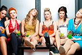 stock photo of leggy  - Women or models in club or disco drinking cocktails having no fun as the party is boring - JPG