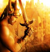 foto of sword  - Portrait of a beautiful young warrior holding sword in golden light - JPG
