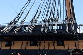 stock photo of sloop  - an old wooden battleships rigging with cannons below - JPG