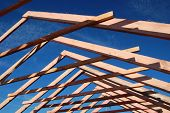 stock photo of gable-roof  - Wood Roof Trusses viewed from inside of new home looking out to a blue sky above  - JPG
