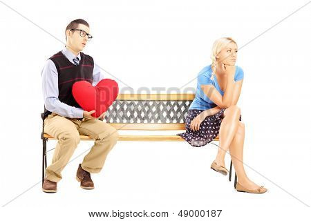 Male holding a red heart and disappointed blond female sitting on a wooden bench isolated on white background