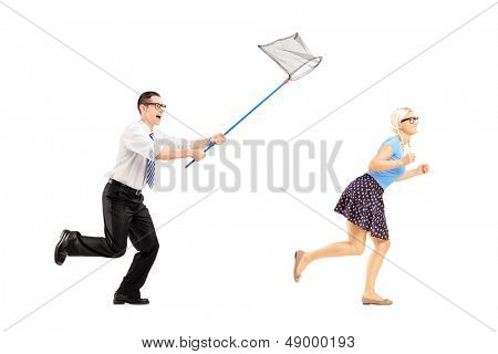 Full length portrait of a young woman trying to runaway from guy with butterfly net isolated on white background