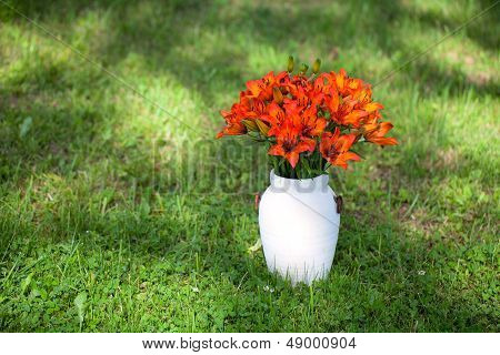 Vase With Orange Lillies On Green Grass