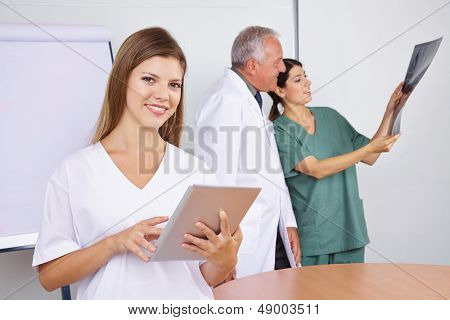 Happy MTA using tablet computer with medial team in background