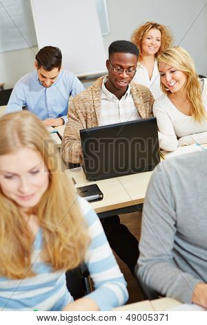 Students studying with laptop computer in class and talking to each other