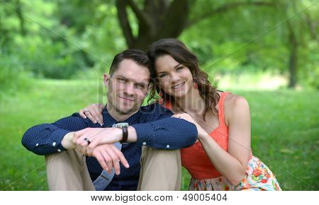Couple sitting on the ground in a garden setting