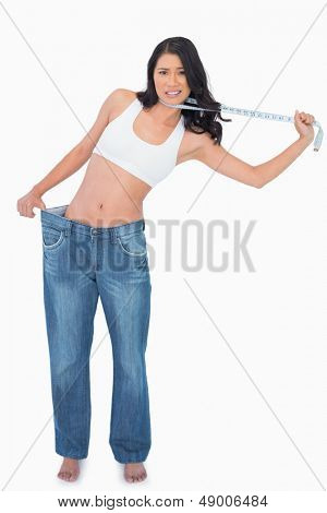Woman wearing too big pants and strangling herself with measuring tape on white background