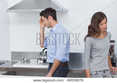 Couple sulking at each other in the kitchen after a dispute