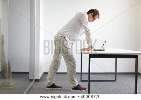 pulsos exercerem durante trabalho de escritório - homem em pé lendo no tablet em seu escritório