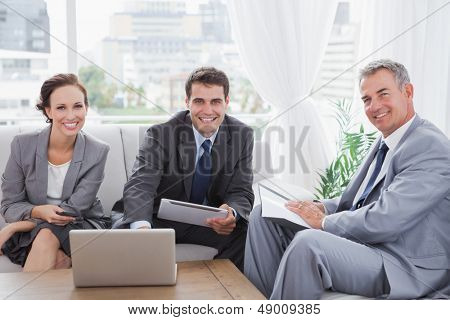 Business people smiling at camera while having a meeting in cosy meeting room
