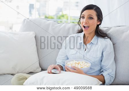 Astonished woman relaxing on the sofa eating popcorn in her living room