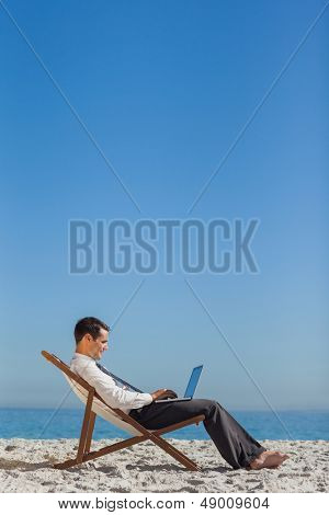 Young businessman on his deck chair using his laptop on the beach