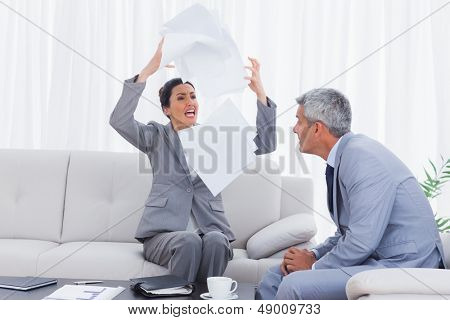 Furious businesswoman throwing documents with colleague watching on the sofa in office