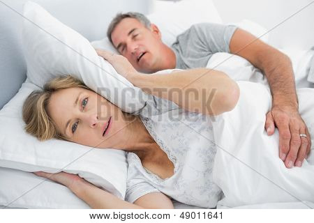 Irritated wife blocking her ears from noise of husband snoring in bedroom at home