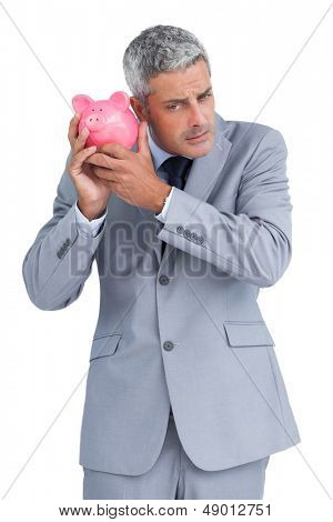 Sceptical businessman on white background holding piggy bank