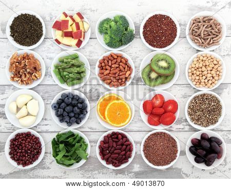Large super food selection in white porcelain dishes over distressed white wooden background.