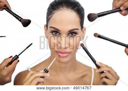 Glamorous woman encircled by make up brushes on white background