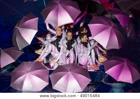 MOSCOW - DEC 21: Girls in costume with umbrellas performing in pool at Show Olympic champions in synchronized swimming in Sports complex Olympic on December 21, 2012 in Moscow, Russia.