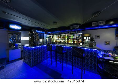 The bar counter in cafe with three chairs illuminated with blue light