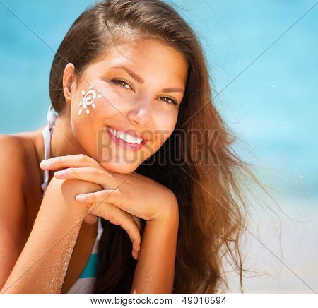 Suntan Lotion Woman Applying Sunscreen Solar Cream. Beautiful happy cute Girl applying Sun Tan Cream on her Face with ocean in background. Sun Tanning. Skin Protection