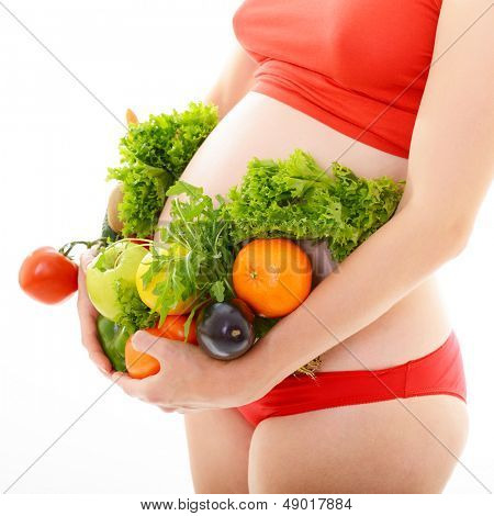 Beautiful pregnant woman in red with fresh fruits and vegetables, healthy life concept, isolated over a white background