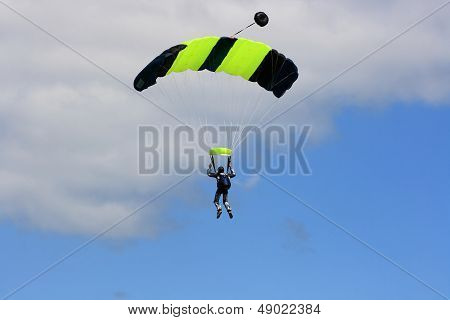 Skydiver Parachuting Down To The Earth.