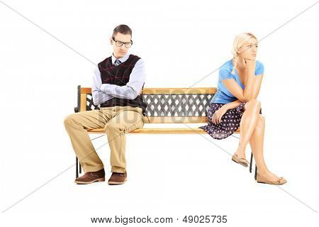 Young couple sitting on a wooden bench after having an argument isolated against white background