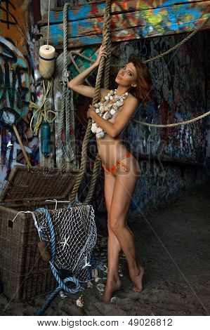 Swimsuit model posing sexy topless wearing seashells necklace and bikini bottom
