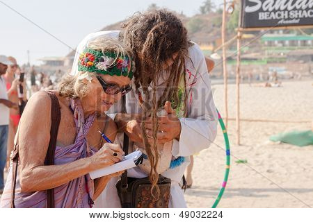 Arambol, Goa - February 5, 2013: An Unidentified Older Woman Writes Something In A Notebook Under Di