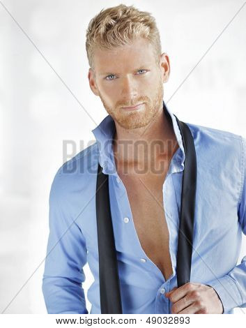 Portrait of a handsome stylish man opening his shirt and unloosening tie