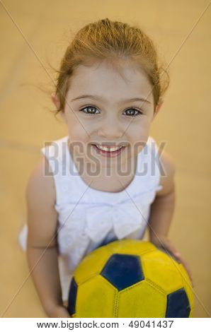 Sweet Girl Playing With Ball Outdoors. Focus On Eye, Natural Ligh