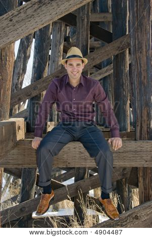 Young Man Sitting On Wooden Beam