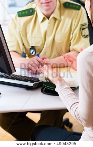 Police officer in police station working on the computer, registering a complaint
