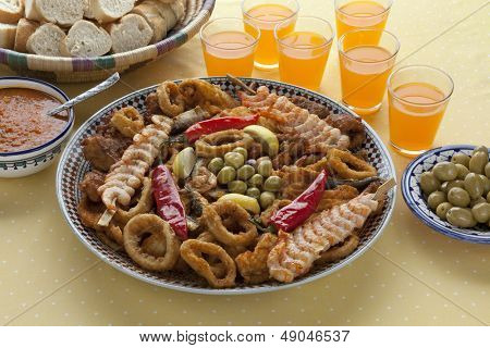 Traditional Moroccan fish dish with sauce,olives and bread