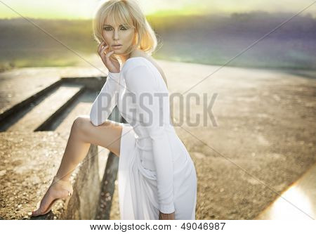 Beautiful blond woman in white dress