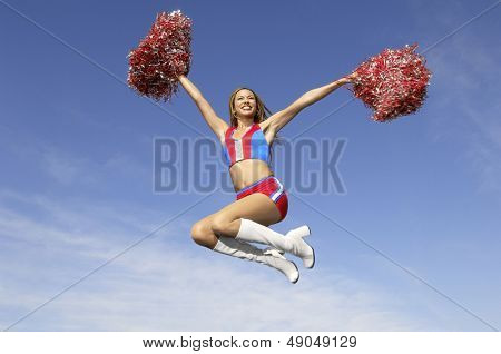 Low angle view of a cheerful cheerleader jumping midair with pom poms against the sky