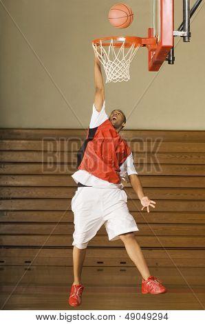 Full length of an African American basketball player missing slam dunk