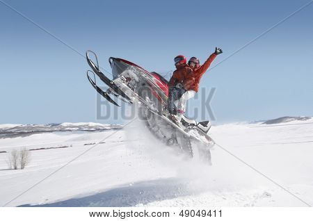 Side view of a couple jumping snowmobile in snow