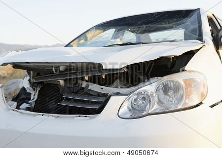 Closeup of a front end of wrecked car on desert highway
