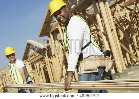 Low angle view of construction workers carrying boards at construction site