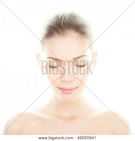 Beauty woman - perfect skin care portrait. Female beauty spa close up of serene relaxed multiracial girl relaxing with eyes closed isolated on white background. Mixed ethnic Asian Chinese / Caucasian.