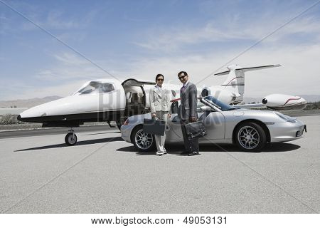 Portrait of a business couple standing in front of convertible and private jet on landing strip