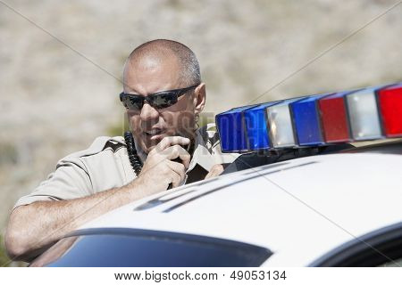 Closeup of a police officer using two way radio by police car
