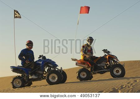 Portrait of young men with helmets sitting on quad bikes in the desert