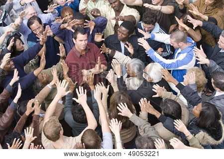 Portrait of a male celebrity standing with hands folded amidst around with fans