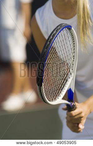 Closeup midsection of a tennis player with racket waiting for doubles partner to serve