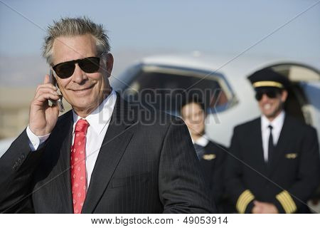 Portrait of smiling businessman on call with blurred pilot and flight attendant standing in the background